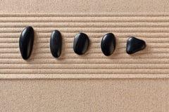 Cinq cailloux noirs sur le sable ratissé Photographie stock