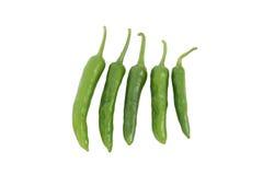 Cinq chillis verts sur le fond blanc Photographie stock libre de droits