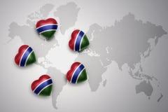 Cinq coeurs avec le drapeau national de la Gambie sur un fond de carte du monde Images libres de droits