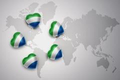 Cinq coeurs avec le drapeau national de la Sierra Leone sur un fond de carte du monde Images stock