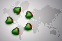 Cinq coeurs avec le drapeau national de la Zambie sur un fond de carte du monde Photos stock