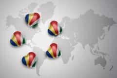Cinq coeurs avec le drapeau national des Seychelles sur un fond de carte du monde Image stock