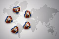 Cinq coeurs avec le drapeau national du Souaziland sur un fond de carte du monde Photos stock