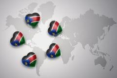 Cinq coeurs avec le drapeau national du Soudan du sud sur un fond de carte du monde Photo libre de droits
