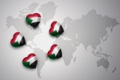 Cinq coeurs avec le drapeau national du Soudan sur un fond de carte du monde Photographie stock libre de droits