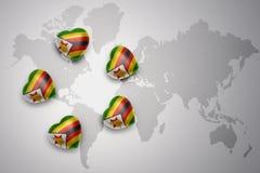 Cinq coeurs avec le drapeau national du Zimbabwe sur un fond de carte du monde Images libres de droits