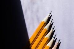 Cinq crayons simples sur un fond pourpre solide dans la lumière contrastante de lumière du soleil dure de la fenêtre avec un e illustration stock