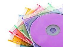 Cinq disques compacts colorés dans la caisse CD en plastique Photographie stock