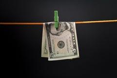 Cinq dollars étaient fixes sur une corde avec une pince à linge verte Photos libres de droits