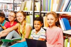 Cinq enfants de sourire s'asseyant dans une rangée sur le plancher Photo libre de droits
