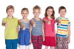 Cinq enfants gais tiennent ses pouces  Photographie stock
