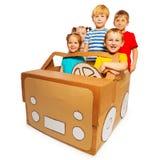 Cinq enfants heureux conduisant la voiture faite main de carton images stock