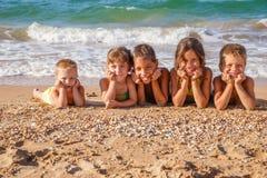 Cinq enfants sur la plage Photo stock