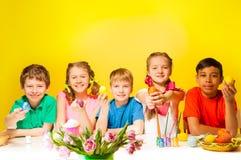 Cinq enfants tenant les oeufs de pâques colorés à la table Photos libres de droits