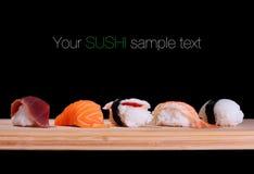 Cinq espèces des sushi de poissons sur le conseil en bambou Image stock