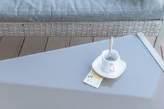 Cinq euros et tasse de café vide sur une table en verre de café extérieur Paiement, astuce photo libre de droits