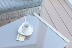 Cinq euros et tasse de café vide sur une table en verre de café extérieur Paiement, astuce photographie stock libre de droits