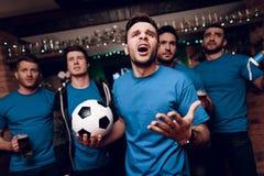 Cinq fans de foot buvant de la bière triste que leur équipe desserre à la barre de sports photographie stock libre de droits
