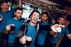 Cinq fans de sports buvant de la bière célébrant et encourageant à la barre de sports Photographie stock libre de droits
