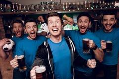 Cinq fans de sports buvant de la bière célébrant et encourageant à la barre de sports Photos libres de droits