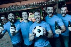 Cinq fans de sports buvant de la bière célébrant et encourageant devant la TV à la barre de sports Images stock