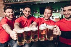 Cinq fans de sports buvant de la bière encourageant à la barre de sports photo libre de droits