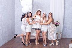 Cinq femmes dans la célébration blanche avec le champagne Images stock