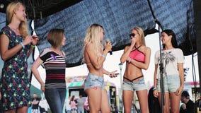Cinq filles beautiuful se tiennent sur l'étape avec la MIC pour une sorte de concurrence banque de vidéos