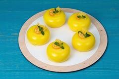 Cinq gâteaux de mousse de mangue avec le lustre de passiflore comestible de passiflore Photographie stock
