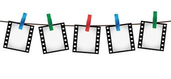 Cinq glissières de film de photo sur une corde avec des clothepins Photos stock