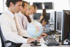 Cinq hommes d'affaires dans le bureau avec un globe de bureau Photographie stock libre de droits