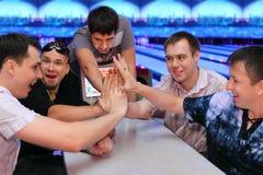 Cinq hommes s'asseyent aux mains de table et de contact dans le bowling Photographie stock libre de droits