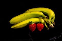 Cinq jaunes et ` vert s de banane et ` s de deux fraises Image libre de droits