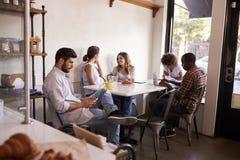 Cinq jeunes adultes traînant à un café photo stock