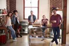 Cinq jeunes amis ayant le café dans le regard de cuisine à l'appareil-photo Image stock