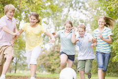 Cinq jeunes amis jouant au football Image stock