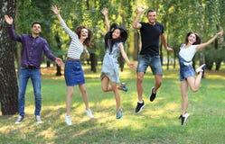 Cinq jeunes femmes et hommes heureux d'amis sautant dehors Photos libres de droits