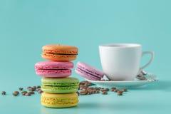 Cinq macarons français colorés et tasse de café photographie stock
