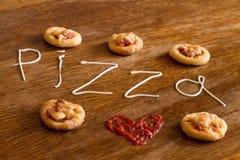 Cinq mini pizzas et texte écrit et x22 ; pizza& x22 ; de la mayonnaise Photographie stock libre de droits