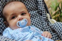 Cinq mois de bébé garçon jouant dans la poussette photographie stock libre de droits