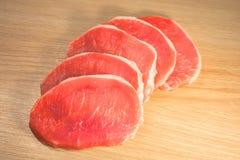 Cinq morceaux de porc coupés et ont empilé comme fan sur un conseil avec une texture en bois Image libre de droits