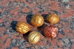 Cinq noix d'or sur le granit Images stock