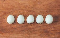 Cinq oeufs épluchés cuits dans une rangée sur une vieille planche à découper Photo libre de droits