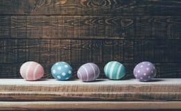 Cinq oeufs de pâques faits main colorés se situent dans une rangée sur une pile de conseils sur un fond en bois Avec le rétro eff Image stock