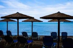 Cinq parapluies rustiques de Palapa situés au rivage de la mer Méditerranée avec plier les chaises bleues au-dessus du sable, bea images stock