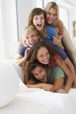 Cinq personnes dans la salle de séjour empilée vers le haut du sourire Images stock