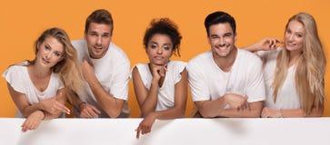 Cinq personnes posant avec le conseil vide blanc photographie stock