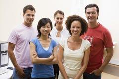 Cinq personnes restant dans le sourire de salle des ordinateurs Images libres de droits