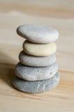 Cinq pierres de zen de station thermale empilées sur un fond en bois Photos libres de droits