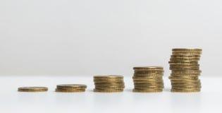 Cinq piles de pièces de monnaie, de petit à grand, sur le fond blanc Rouble russe Photos libres de droits